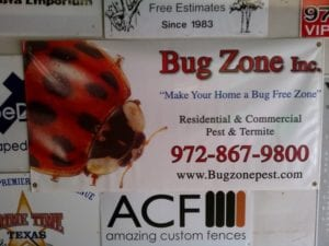 White sign with large lady bug advertising a pest & termite company