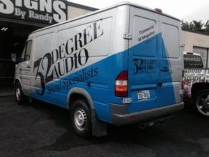 Blue and white work van with black vinyl decal lettering