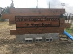 Cement and wooden sign for arborilogical services company