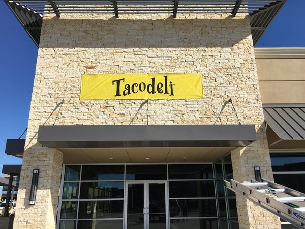 Storefront of Mexican restaurant with large yellow banner that says Tacodeli
