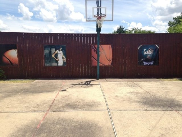 Four basketball themed banners installed on a fence surrounding a basketball court