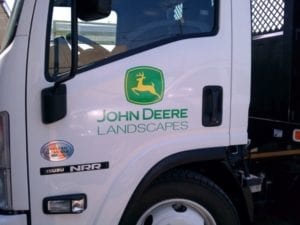 Close up of 18-wheeler cabin door with John Deer Landscapes vinyl decals