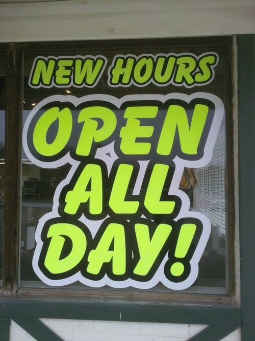 Bold neon window decals that says New Hours Open All Day