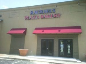 Purple and pink storefront sign for Rachael's Plaza Bakery