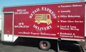 Large red enclosed trailer with vinyl decals for a delivery company