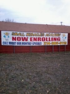 Large white banner on fence for children's academy