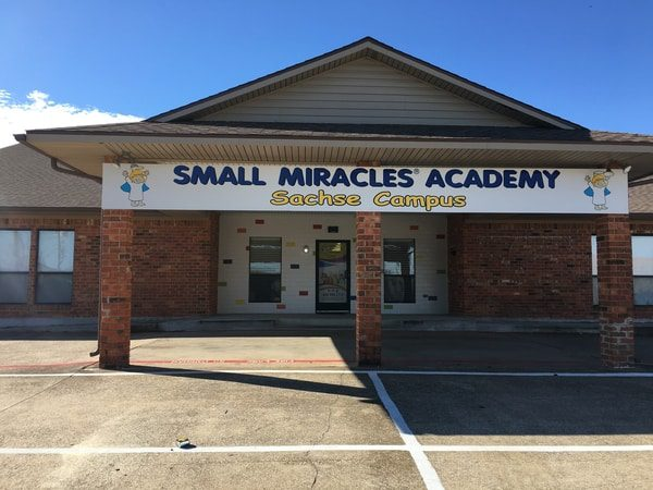 White outdoor banner for Small Miracles Academy