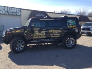 Large Hummer with vinyl decals for a tree services company