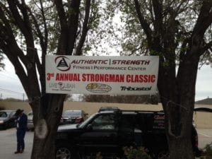 White banner for strongman competition hung between two trees