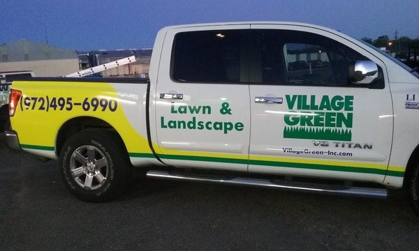 White work truck with green and yellow decals for a lawn and landscape company