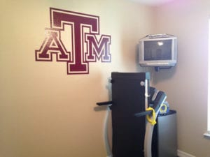 ATM university logos on wall in workout room