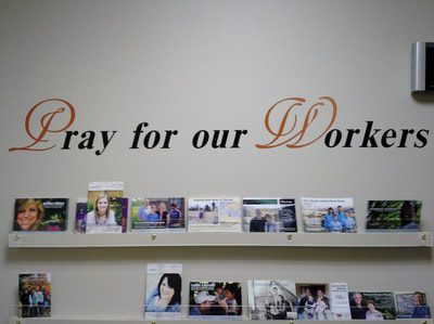 White wall with vinyl decal lettering that says pray for our workers