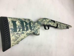 Rifle with camouflage wrap and initials decal