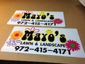 Two car magnets on a table advertising a lawn and landscape company