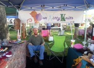 Man in chair under tent at a booth for a knitting company