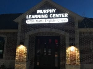 The exterior of a building at night with a lit storefront sign for Murphy Learning Center