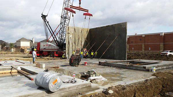 Image of workers and a crane installing two walls of a new commercial building