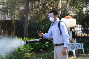 man misting bushes to get rid of mosquitos
