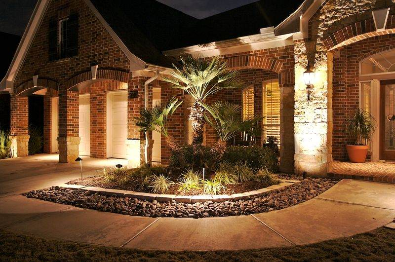 flower bed in front of a house with landscape lighting