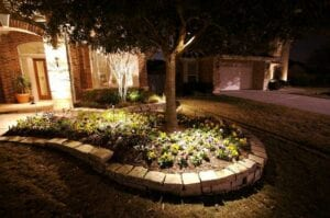 flower bed in front of a home with outdoor lighting