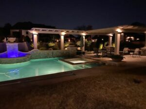 backyard pool and seating area lit up with outdoor lighting