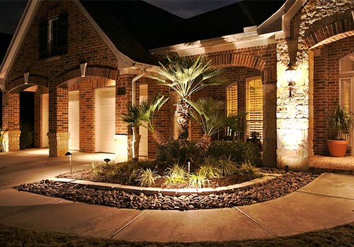 accent lighting around a flower bed in front of a home