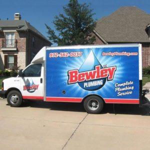 Bewley Plumbing box truck in front of a residential street with beautiful homes behind it