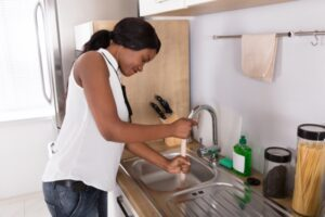 A woman trying to unclog her sink with a plunger.