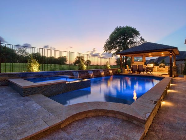 lighted pool at sunset with outdoor kitchen