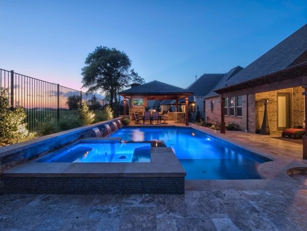 wide shot of a pool and outdoor kitchen at night