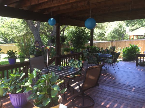 Backyard deck with patio furniture and plants under a pergola