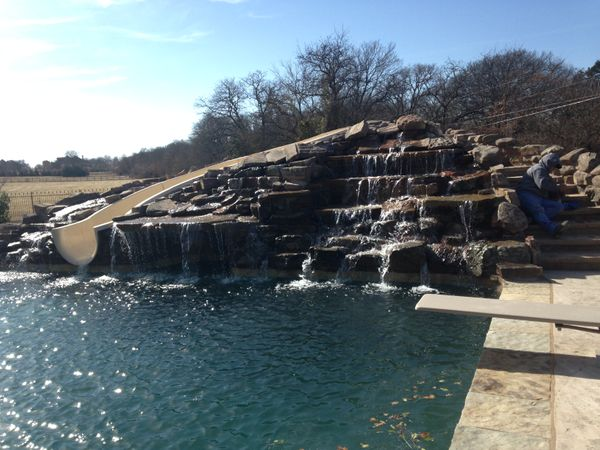 A pool with a decorative stonework waterfall and slide