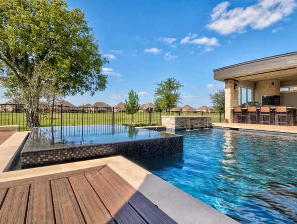 spa with black glass tile and pool