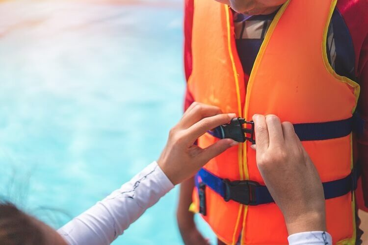 A mother helps her child don a life vest