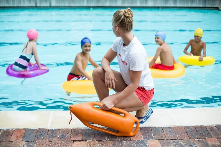 A lifeguard watches over swimming children