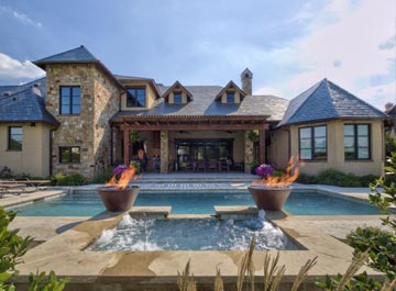 image of a pool water feature with pool and house in background