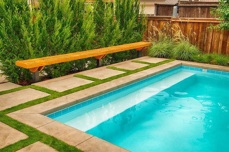 Close up of rectangular swimming pool edge with wooden bench on the deck and landscaping