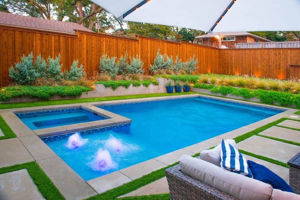Nice custom rectangle pool with modern landscaping in a backyard