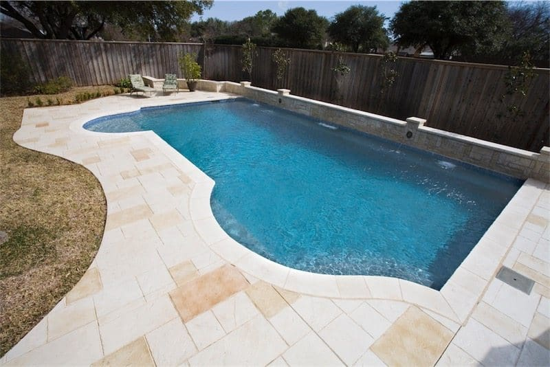Custom pool with concrete patio deck and water feature