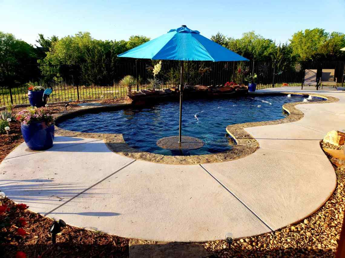 A freeform pool with an umbrella table and a custom pool deck