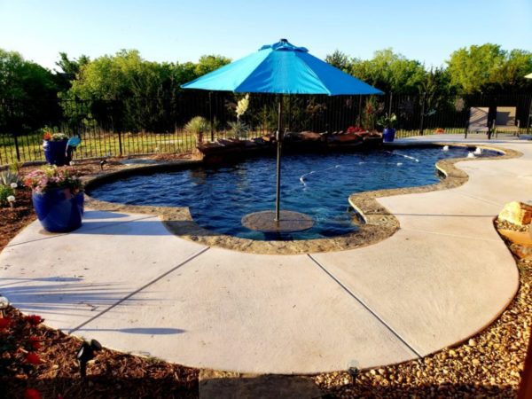 We love the design work on this newly constructed pool - and we appreciate the feedback from our customer. The umbrella was our customer's idea and we worked with them to create a custom table to match their pool coping. It's small details like this that truly matter and really give your pool a custom approach that few other pool builders take the time to complete. We love this type of work and thoroughly enjoy a challenge to always come up with new looks for your home!