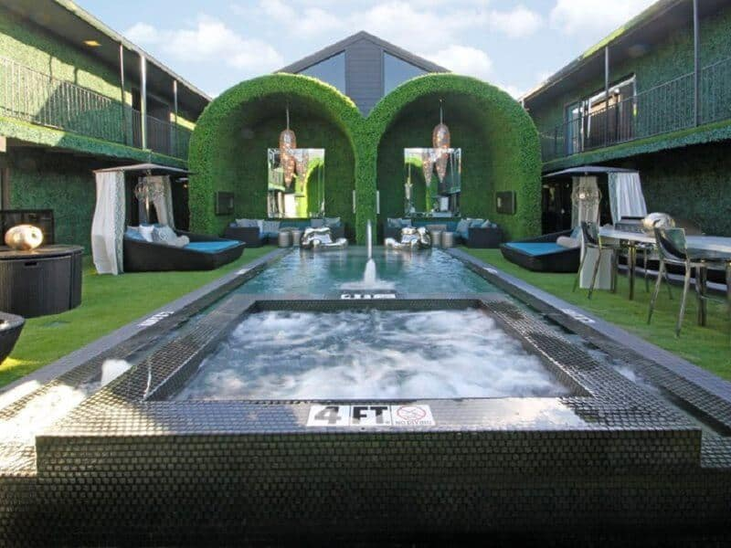 Commercial pool surrounded by lounge chairs and a green canopy