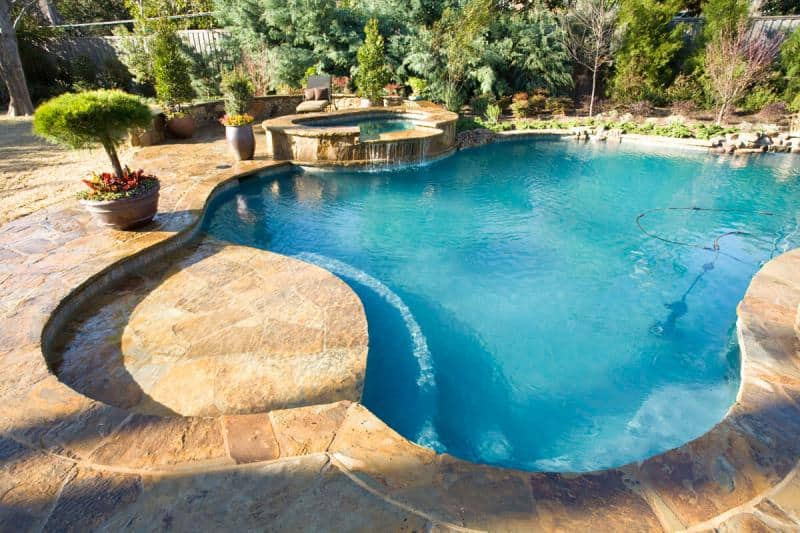 Free-form pool surrounded by a deck and landscaping
