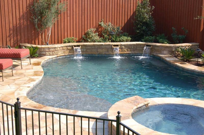 Pool sourounded by lounge chairs and landscaping