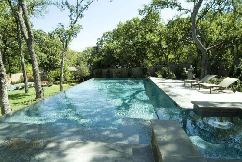 Infinity pool surrounded by landscaping and a basketball court