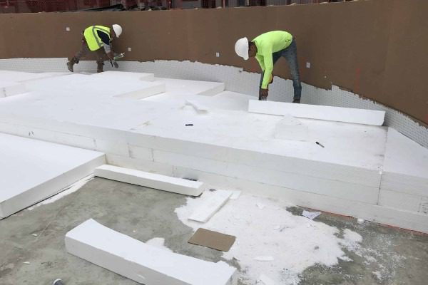 Two construction workers lay geofoam at the base of a pool