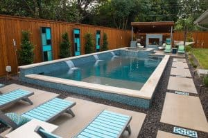 Geometric pool surrounded by landscaping and modern decor