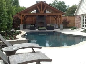 Full view of a backyard with a pool and a fireplace surrounded by chairs
