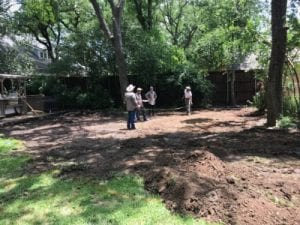 Four men stand on a dirt patch discussing a pool build