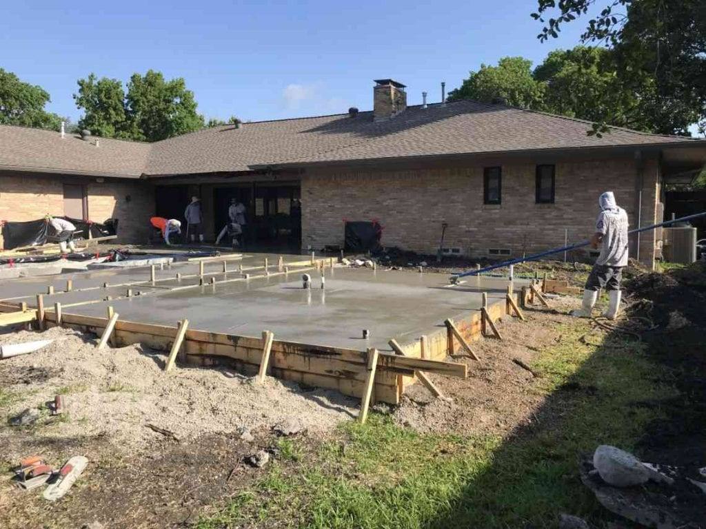A worker smooths a recently poured concrete deck with a house and some other workers in the background